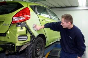 Mitarbeiter von Autolackierung Zech prüft Karosserie