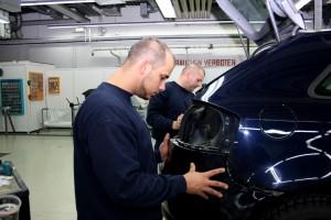 Mitarbeiter von Autolackierung Zech arbeitet an Karosserie eine PKWs